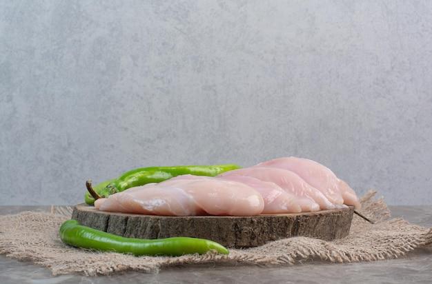 Rohes hühnerfleisch mit paprika auf holzbrett. foto in hoher qualität