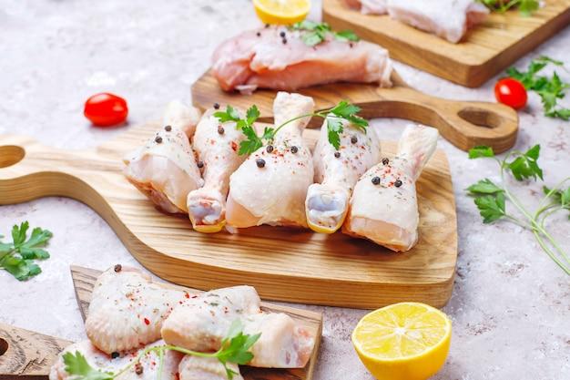 Rohes hühnerfleischfilet, oberschenkel, flügel und beine mit kräutern, gewürzen, zitrone und knoblauch. ansicht von oben