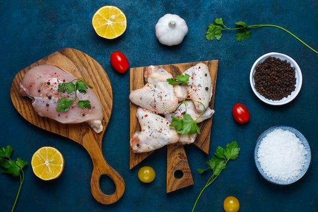 Rohes hühnerfleischfilet, -schenkel, -flügel und -beine mit kräutern, gewürzen, zitrone und knoblauch auf dunkelblauem hintergrund. ansicht von oben