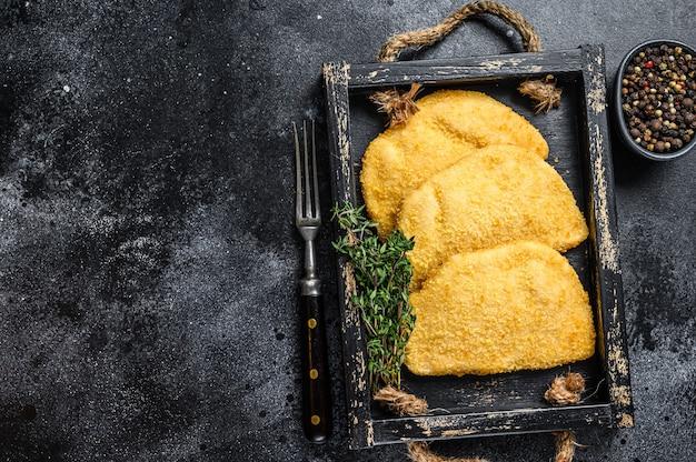 Rohes huhn cordon bleu fleisch schnitzel in einem holztablett mit kräutern auf holztisch. draufsicht.