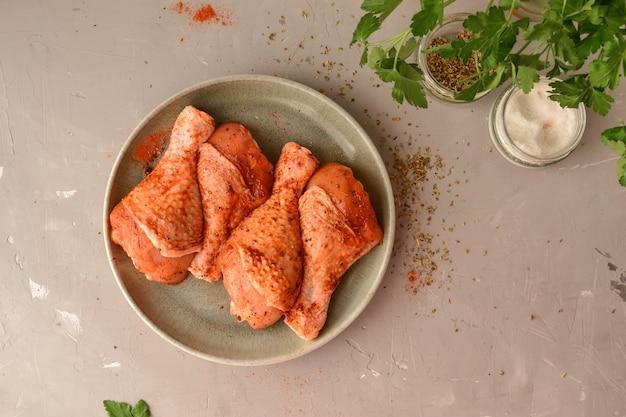 Rohes huhn in einem teller. mariniertes fleisch mit oregano, kräutern und paprika. rohe hähnchenschenkel, schritt für schritt kochen. draufsicht, graue lichtfläche