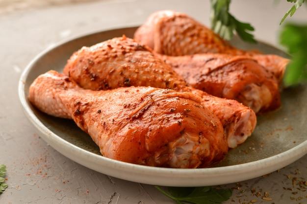 Rohes huhn in einem teller. mariniertes fleisch mit oregano, kräutern und paprika. rohe hähnchenschenkel, schritt für schritt kochen. nahaufnahme, graue lichtfläche.