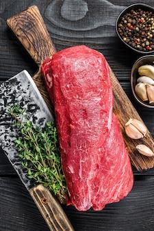 Rohes kalbsfleisch vom filet für steaksfilet mignon auf einem hölzernen schneidebrett mit metzgerbeil