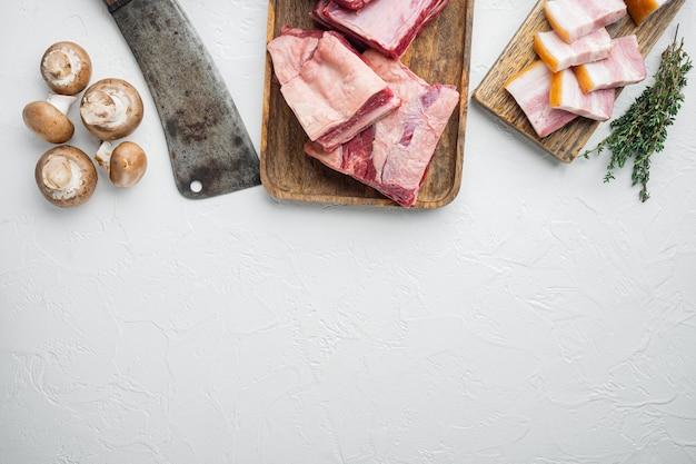 Rohes kalbskälber-kurzrippenfleisch-set, mit zutaten und altem metzger-hackmesser, auf weißem steinhintergrund, draufsicht flach gelegt, mit kopierraum für text