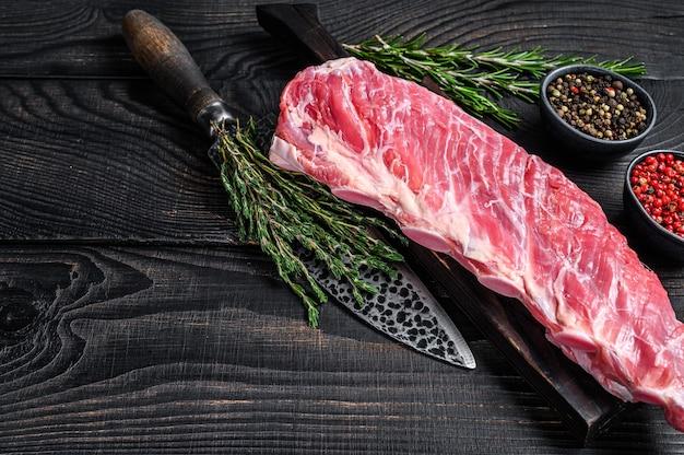 Rohes kalbskälber-rippchenfleisch mit fleischermesser.