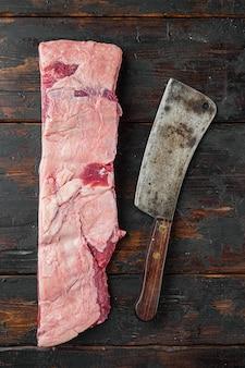 Rohes kalbskalb-kurzrippenfleischset und altes fleischbeilmesser auf altem dunklem holztischhintergrund, draufsicht flach legen