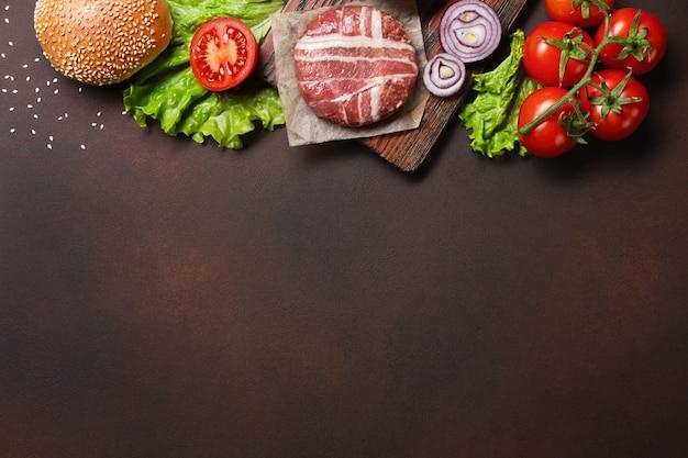 Rohes kotelett, tomaten, kopfsalat, brötchen, käse, gurken und zwiebel der hamburgerbestandteile auf rostigem hintergrund