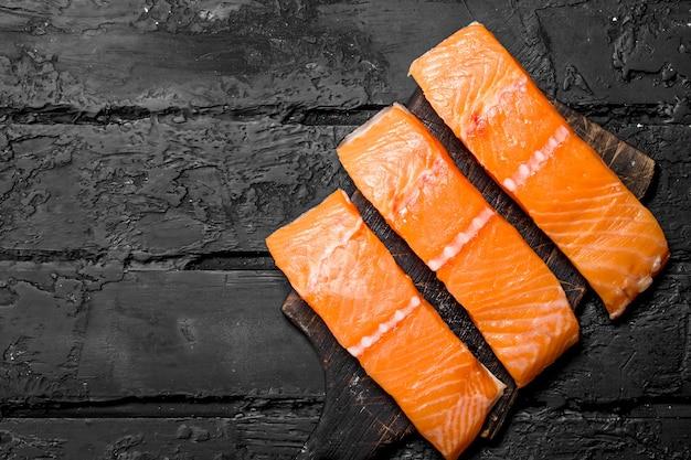 Rohes lachsfischfilet auf schneidebrett. auf schwarz rustikal.