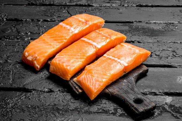 Rohes lachsfischfilet auf schneidebrett. auf schwarzem rustikalem tisch.