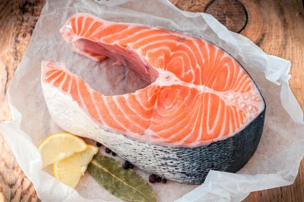 Rohes lachsfischsteak mit zitrone und gewürzen auf hölzernem rustikalem