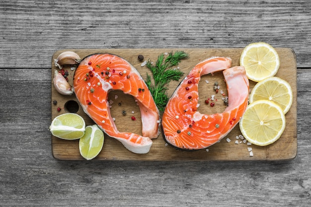 Rohes lachssteak mit kräutern, zitrone und pfefferkörnern auf holzschneidebrett. gesunde und diätnahrung