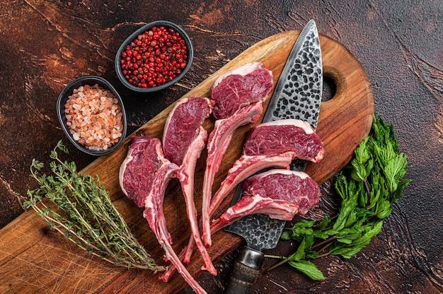 Rohes lamm, hammelkoteletts steaks auf einem holzbrett. dunkler hintergrund. ansicht von oben.