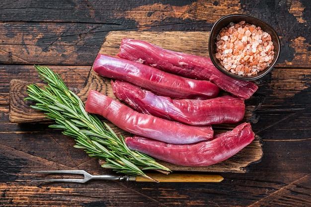 Rohes lammfiletfilet, hammelfleischfleisch auf holzbrett mit kräutern. dunkler holztisch. draufsicht.