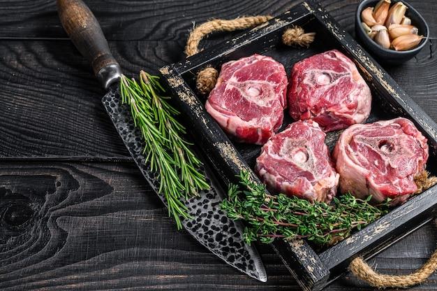 Rohes lammhalsfleisch auf einem metzgertisch mit messer. schwarzer hölzerner hintergrund. ansicht von oben. platz kopieren.