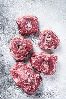 Rohes lammhalsfleisch auf kochtisch auf weißem tisch. draufsicht.