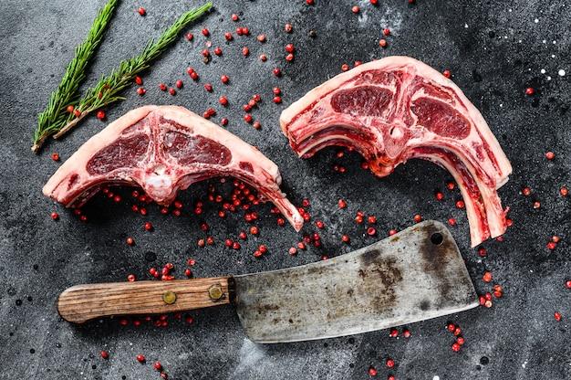 Rohes lammkotelett frisch geschnitten mit fleischerbeil. schwarze oberfläche. draufsicht
