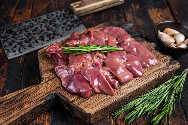 Rohes leberhühner-innereienfleisch auf einem hölzernen schneidebrett mit metzgerbeil