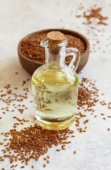 Rohes leinsamenöl und samen mit einem löffel auf weißem tisch hautnah
