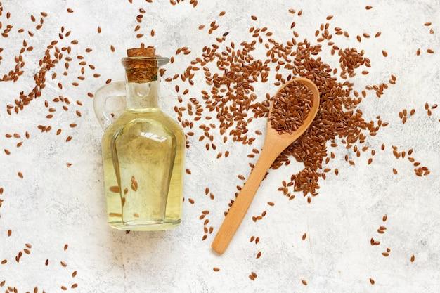 Rohes leinsamenöl und samen mit einem löffel draufsicht auf weißen tisch