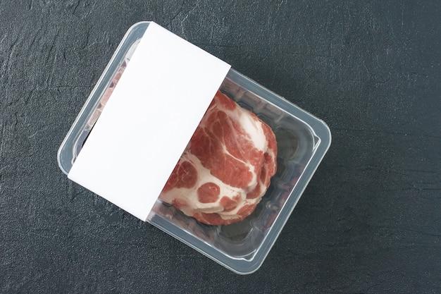 Rohes marmoriertes schweinesteak in vakuumverpackung auf schwarzem hintergrund, draufsicht, logomodell für design