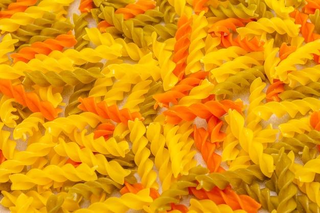 Rohes mehrfarbiges fuzilli auf steinoberfläche. traditionelle italienische pasta, vorbereitung für kinder, ansicht von oben. kochen des tapetenkonzeptes, makro