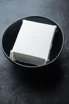 Rohes organisches weißes feta-käse-set auf schwarz