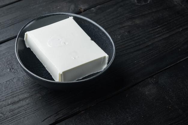 Rohes organisches weißes feta-käseset auf schwarzem holztisch