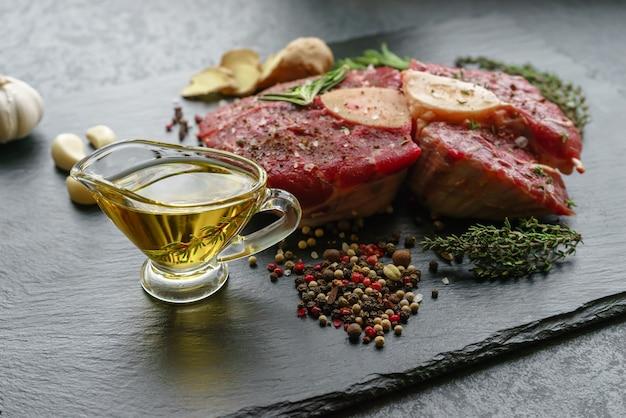 Rohes osso buco steak auf einem schwarzen stein, umgeben von gewürzen