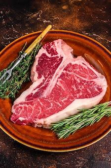 Rohes porterhouse-rindfleisch steak mit kräutern auf einem teller. dunkler hintergrund. ansicht von oben.