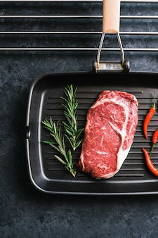 Rohes rib-eye-rindersteak auf schwarzer grillpfanne mit chili-pfeffer und rosmarin