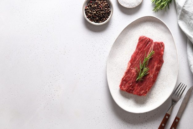 Rohes ribeye-steak mit rosmarin auf weiß. speicherplatz kopieren.