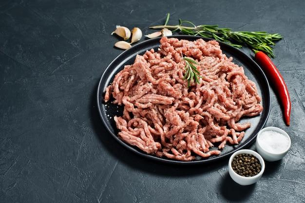 Rohes rinderhackfleisch auf einem steinbrett. zutaten zum kochen, rosmarin, chili, knoblauch, salz.