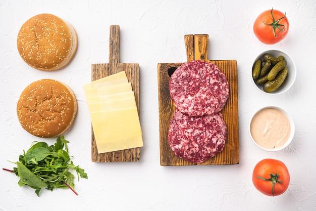 Rohes rinderhackfleisch burger-steakkoteletts mit zutaten und brötchen-set, auf weißem stein