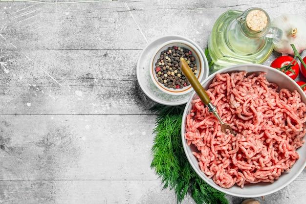 Rohes rinderhackfleisch mit gewürzen und kräutern auf einem rustikalen tisch.