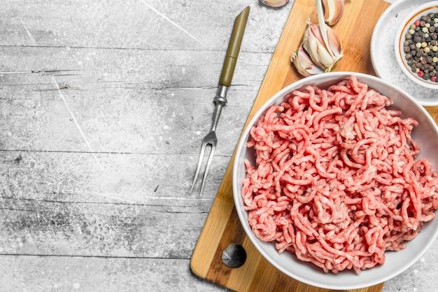 Rohes rinderhackfleisch mit gewürzen und kräutern auf rustikalem tisch.
