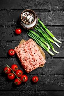 Rohes rinderhackfleisch mit tomaten und frühlingszwiebeln. auf schwarzem rustikalem hintergrund.