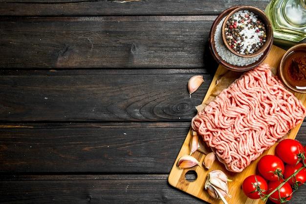 Rohes rinderhackfleisch mit tomaten und gewürzen.