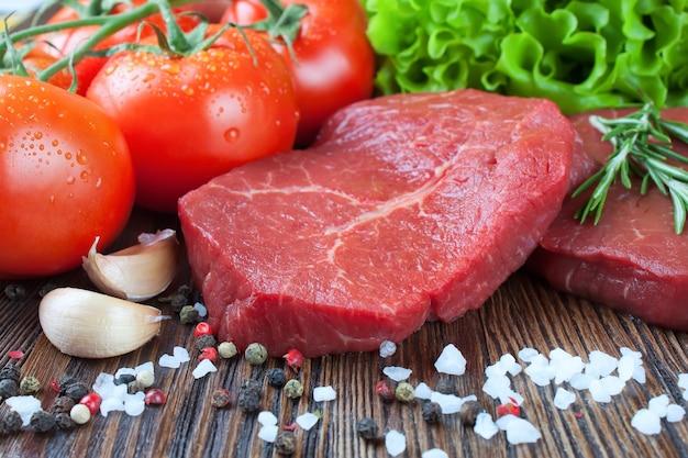 Rohes rindersteak auf schneidebrett mit gemüse und gewürzen auf braunem holzhintergrund. rindersteak, tomate, salat, knoblauch, rosmarin, gewürz.