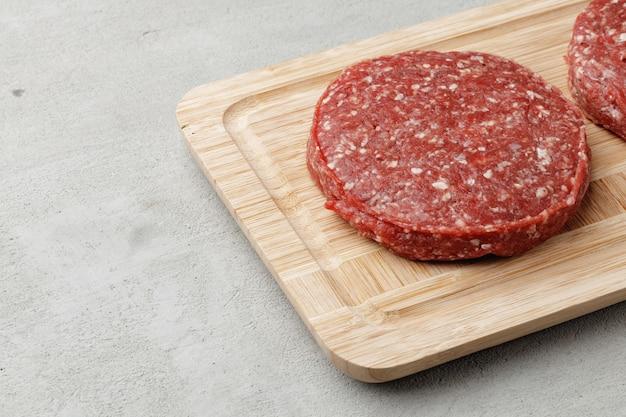 Rohes rindfleisch-burger-pastetchen auf holzbrett
