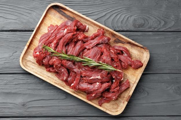 Rohes rindfleisch in scheiben geschnitten auf holzbrett