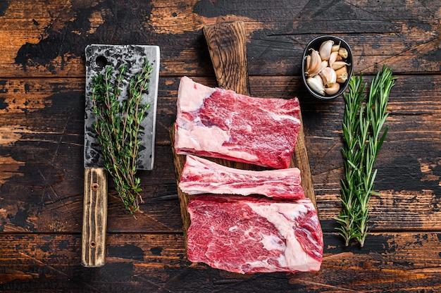 Rohes rindfleisch kalb kurze rippen fleisch auf einem metzger schneidebrett mit hackmesser. dunkler hölzerner hintergrund. draufsicht.