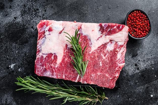 Rohes rindfleisch kurze rippen kalbi auf marmorbrett. schwarzer hintergrund. draufsicht.
