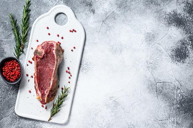 Rohes rindfleisch mit knochen geschnitten. grauer hintergrund. ansicht von oben. platz für text