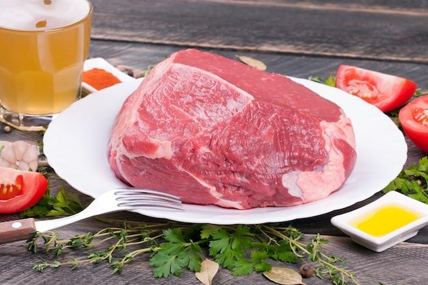 Rohes rindfleisch mit kräutern, gewürzen, gemüse und bier in einem glas auf einem hölzernen hintergrund