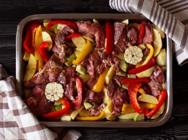 Rohes rindfleisch mit rohem gemüse: zucchini, knoblauch, roter und gelber pfeffer mit natürlichen gewürzen und kräutern
