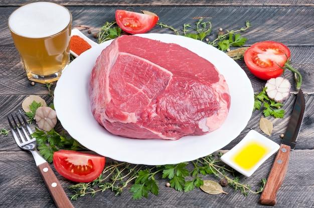 Rohes rindfleisch mit thymian, gewürzen, tomaten, olivenöl, kräutern und bier in einem glas auf einem hölzernen hintergrund