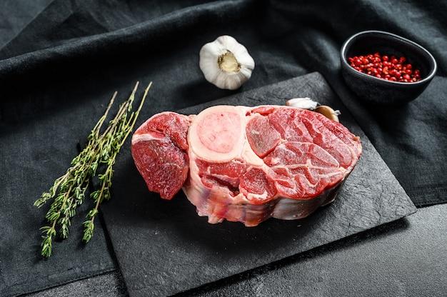 Rohes rindfleisch ossobuco auf einem tisch mit gewürzen. schwarzer hintergrund.