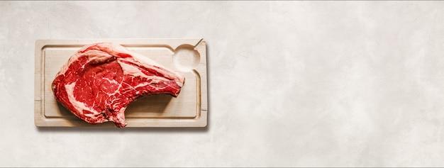 Rohes rindfleisch prime rib und holzbrett isoliert auf weißem beton hintergrund. ansicht von oben. horizontales banner
