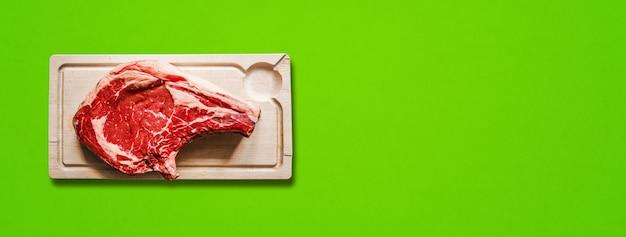 Rohes rindfleisch prime rib und holzschneidebrett auf grünem hintergrund isoliert. ansicht von oben. horizontales banner