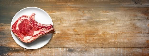 Rohes rindfleisch prime rib und platte auf alten hölzernen hintergrund isoliert. ansicht von oben. horizontales banner